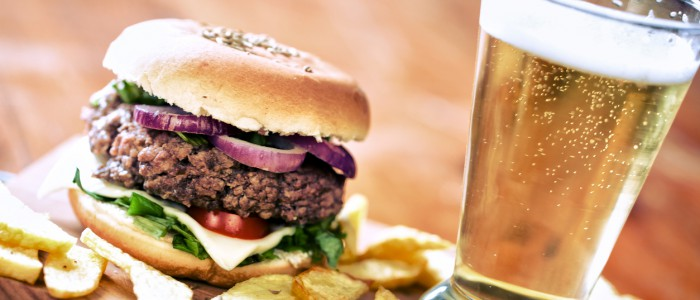 Beef bagel hamburger with potato wedges and fresh beer